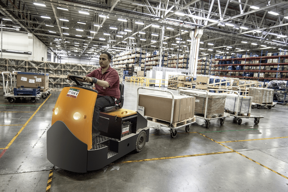 Man driving shrink wrapped boxes around a warehouse
