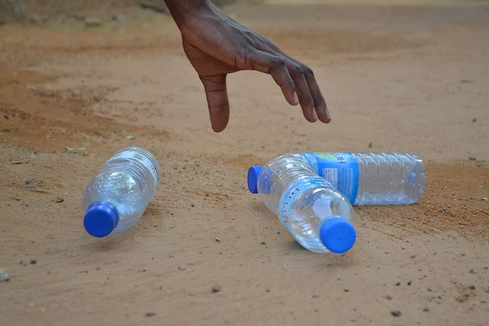 Polyethylene bottles being picked up from a beach